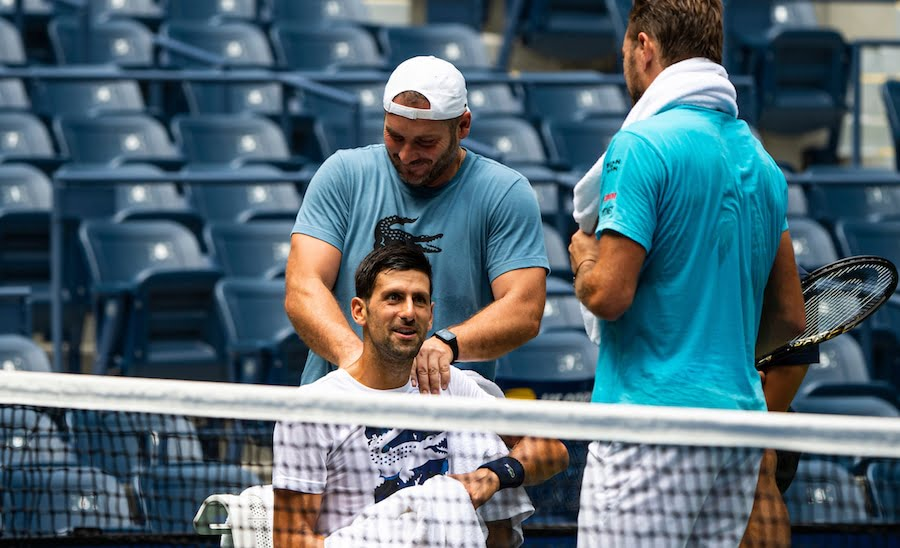 Novak Djokovic receives should treatment whilst chatting to Wawrinka in practise.jpg